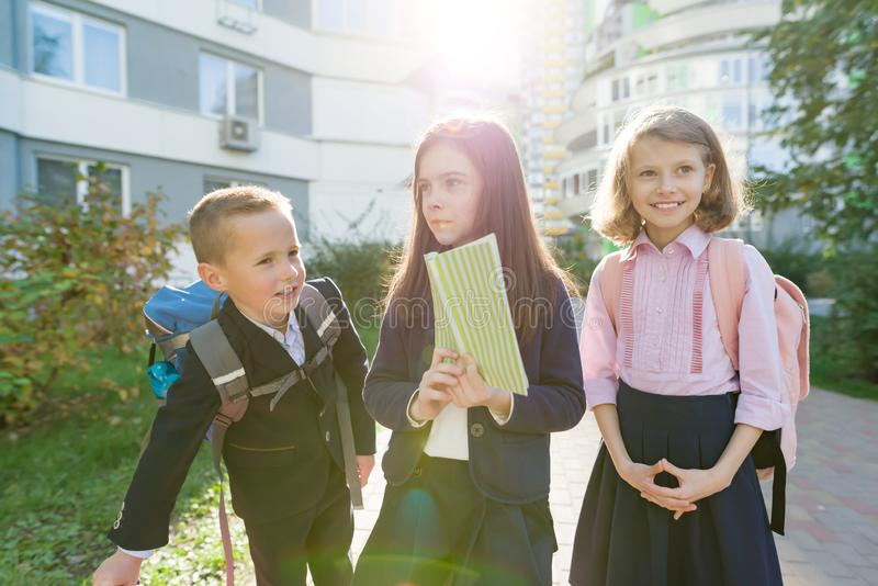 Outdoor portrait of smiling schoolchildren in elementary school. Group of kids with backpacks are having fun, talking, reading a royalty free stock photo