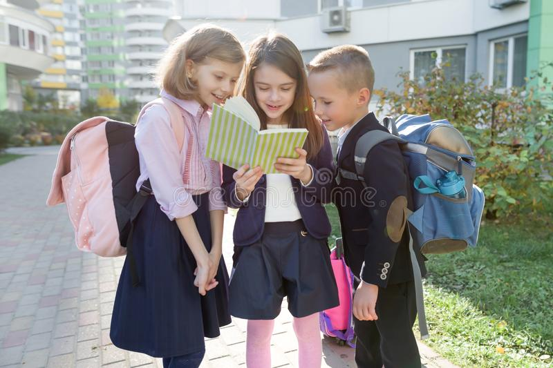 Outdoor portrait of smiling schoolchildren in elementary school. Group of kids with backpacks are having fun, talking, reading a stock photography