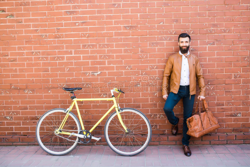 Outdoor portrait of standing bearded hipster with bag in hand near fixed bicycle against brick wall royalty free stock photo