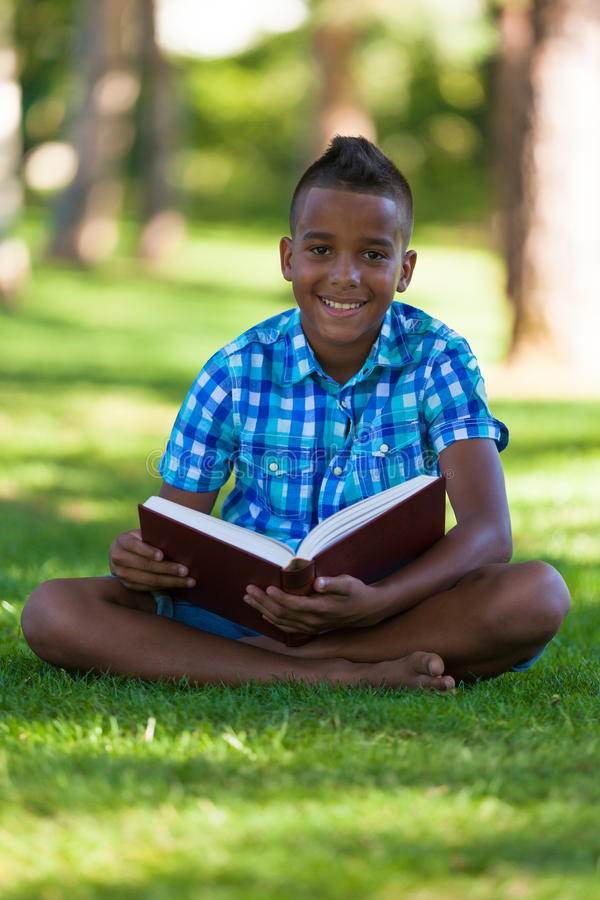 Outdoor portrait of student black boy reading a book stock image