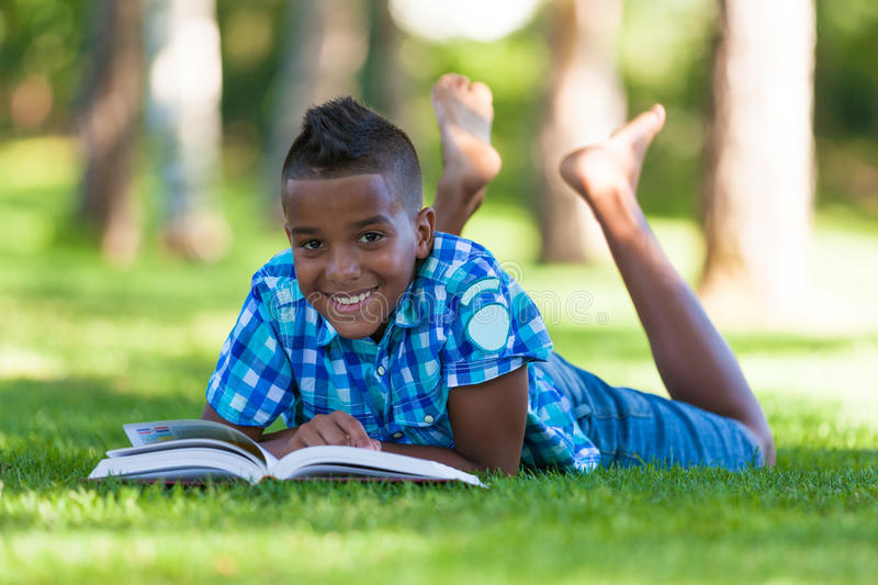 Outdoor portrait of student black boy reading a book royalty free stock photo