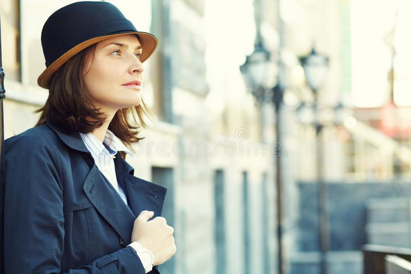 Outdoor portrait of a stylish woman with hat in street royalty free stock images