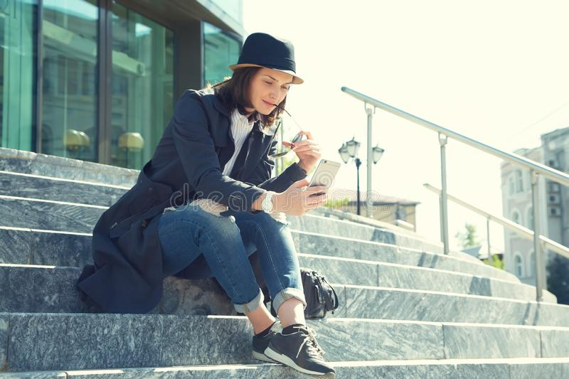 Portrait of a stylish woman in hat and sunglasses with smartphone stock images