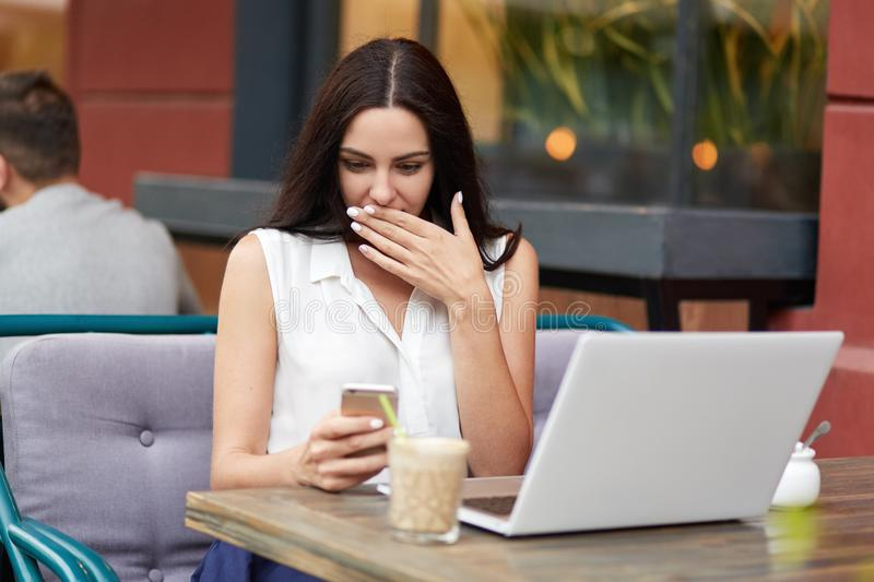 Outdoor portrait of surprised brunette female stares at screen of mobile phone as recieves unexpected message, works freelance on. Laptop computer, sits alone stock photography