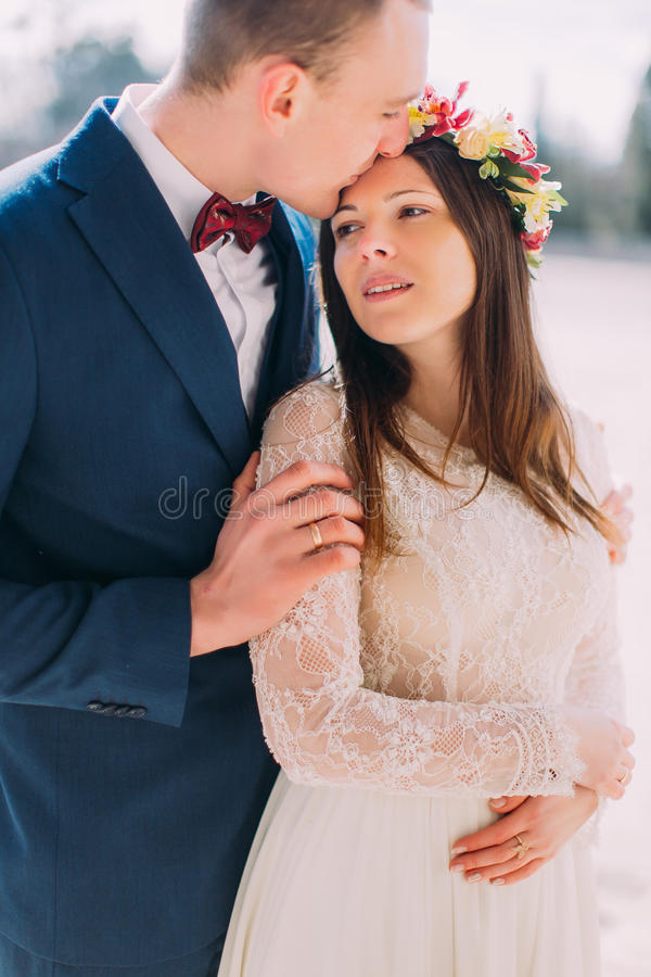 Outdoor portrait of sweet sensual wedding couple embracing. Handsome groom holding his pretty new wife and kisses her in stock photo