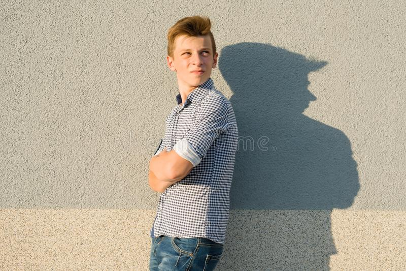 Outdoor portrait of teen boy 14, 15 years old. Gray wall background, copy space stock photography