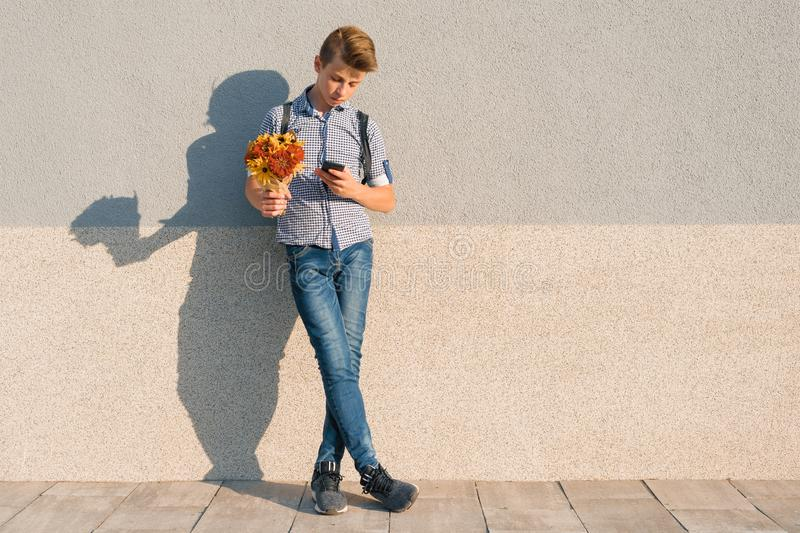 Outdoor portrait of teenage boy with bouquet of flowers, reading text on smartphone, gray wall background copy space.  stock photo