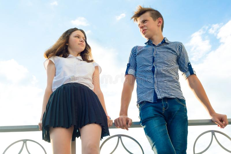 Outdoor portrait of teenage children. Boy and girl 14,15 years old, talking against the blue sky. royalty free stock photo