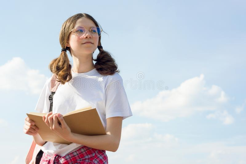 Outdoor portrait of teenager girl reading book. Girl student in glasses with backpack sky background with clouds stock photos