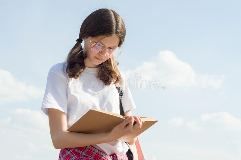 Outdoor portrait of teenager girl reading book. Girl student in glasses with backpack sky background with clouds royalty free stock photos