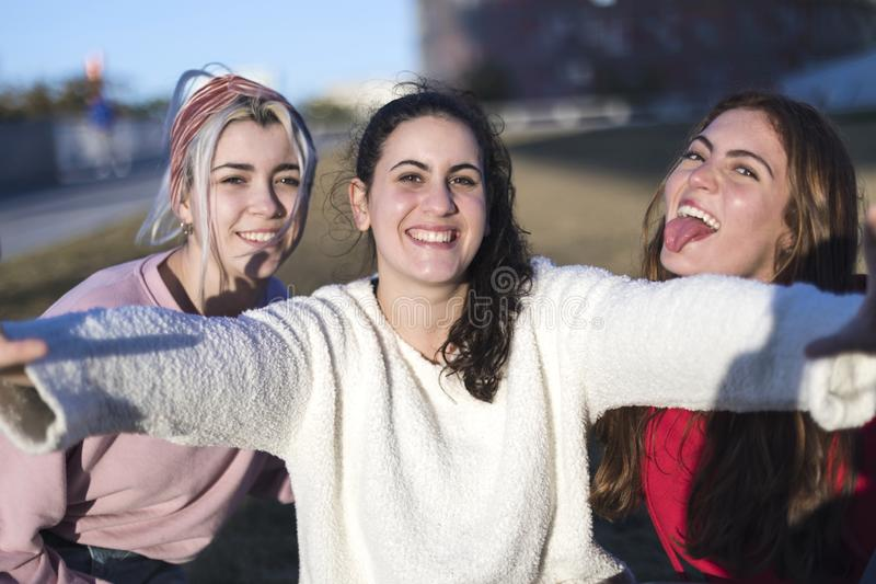 Outdoor portrait of three friends fun girls taking photos with a smartphone at bright sunset royalty free stock images