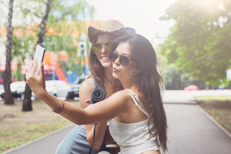 Outdoor portrait of three friends take selfie with smartphone. Two girls friends outdoors take selfie with smartphone. Young female tourists in boho chic fashion stock image