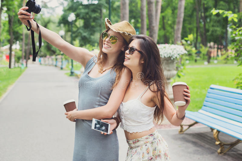 Outdoor portrait of three friends take selfie with smartphone. Two girls friends outdoors take selfie with smartphone. Young female tourists in boho chic fashion royalty free stock images