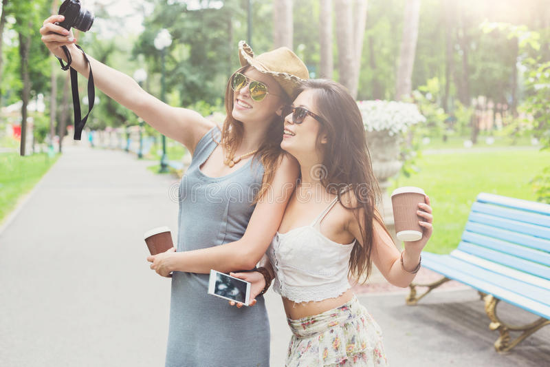 Outdoor portrait of three friends take selfie with smartphone. Two girls friends tourists make selfie. Young females in boho chic fashion clothes, laighing and stock image