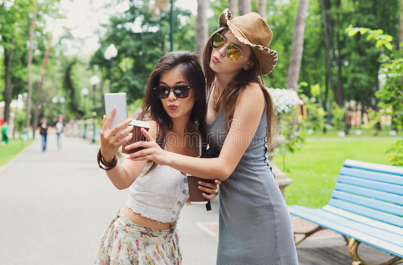 Outdoor portrait of three friends take selfie with smartphone. Two girls friends take selfie with smartphone. Young female tourists in boho chic fashion clothes stock images