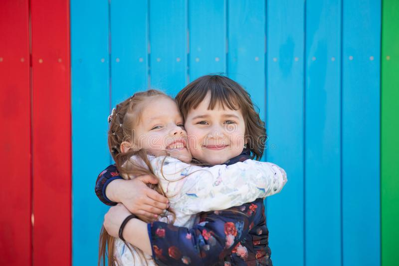 Outdoor portrait of two embracing cute little girls royalty free stock photos
