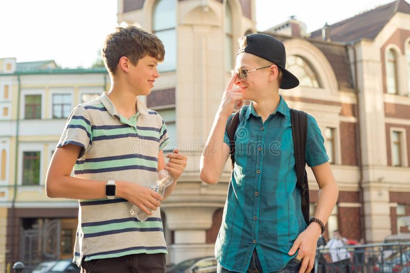Outdoor portrait of two friends boys teenagers 13, 14 years old talking and laughing on city street.  royalty free stock images