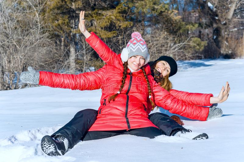 Outdoor portrait of two girls have fun and enjoy the fresh snow on a beautiful winter day in winter park. stock photography