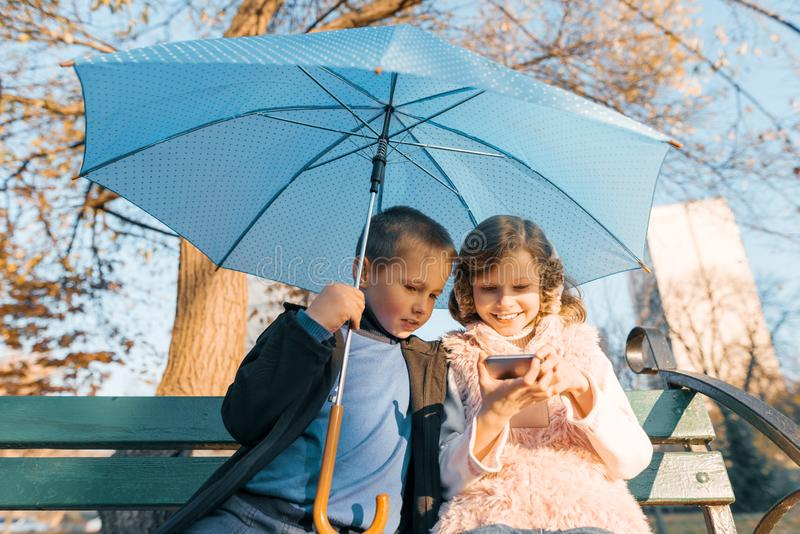 Outdoor portrait of two smiling children of boy and girl, sitting under an umbrella on bench in the park, looking at smartphone, stock images