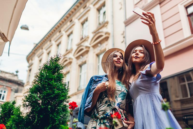 Outdoor portrait of two young beautiful women taking selfie using phone. Girls having fun in city. Best friends royalty free stock images
