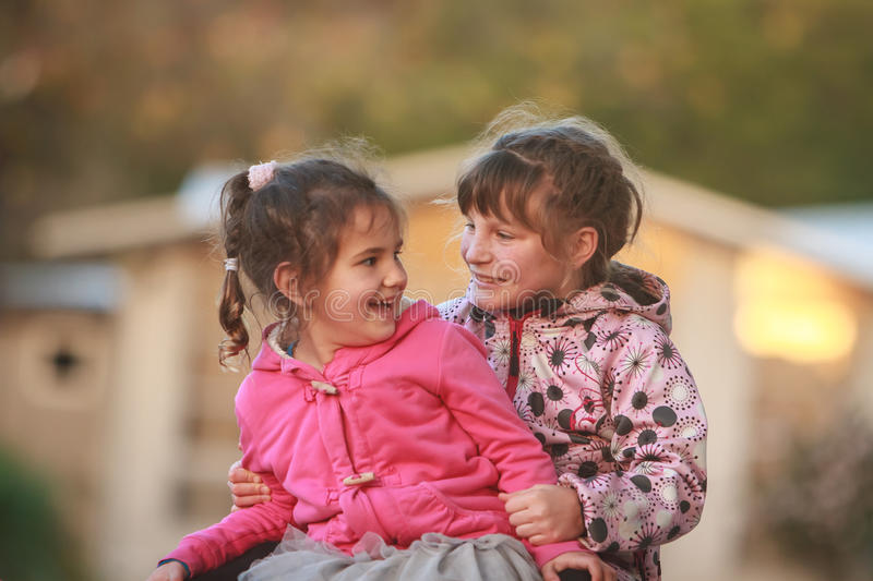 Outdoor portrait of two young happy children, girls - sisters - stock photography
