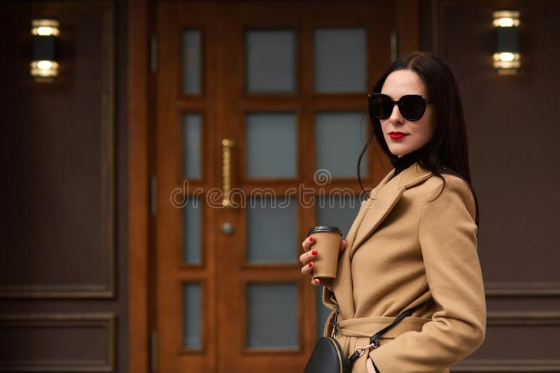Outdoor portrait of a young attractive stylish woman wearing suitable accessories, beige trendy coat, holding a paper cup of stock images