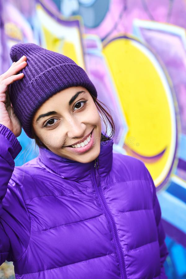 Outdoor portrait of young attractive woman wearing in violet down jacket and knitted hat, smiling to the camera and royalty free stock photos
