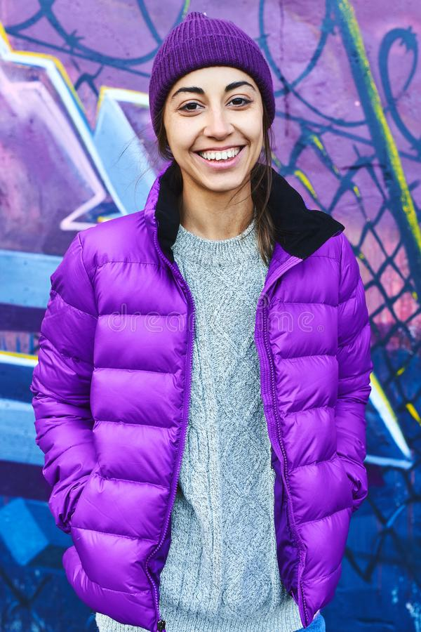 Outdoor portrait of young attractive woman wearing in violet down jacket and knitted hat, smiling to the camera and stock photography