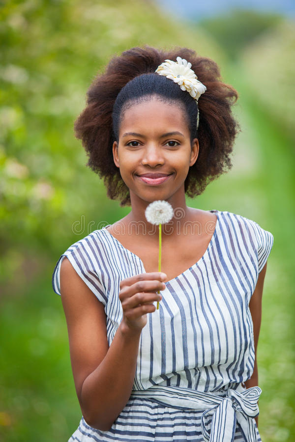 Outdoor portrait of a young beautiful african american woman holding a dandelion flower - Black people stock image