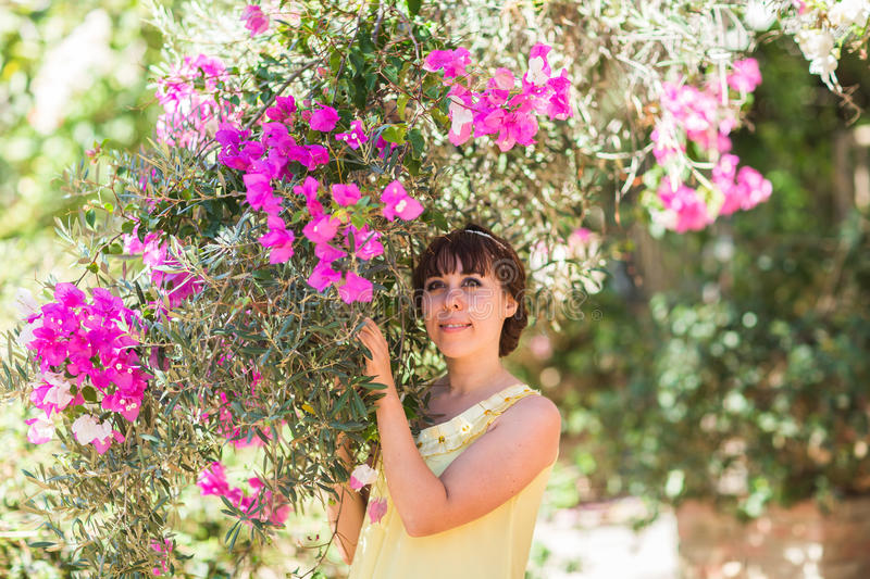 Outdoor portrait of young beautiful fashionable lady posing near flowering tree. Girl looking aside. stock photos
