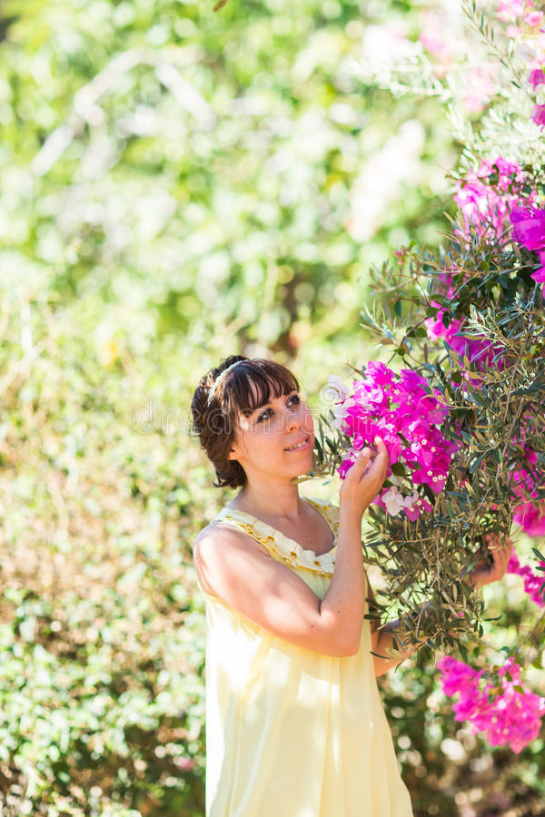 Outdoor portrait of young beautiful fashionable lady posing near flowering tree. Girl looking aside. royalty free stock photos