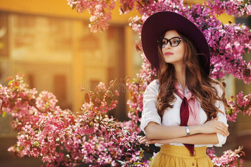 Outdoor portrait of young beautiful fashionable lady posing near flowering tree. Model wearing stylish accessories and royalty free stock image