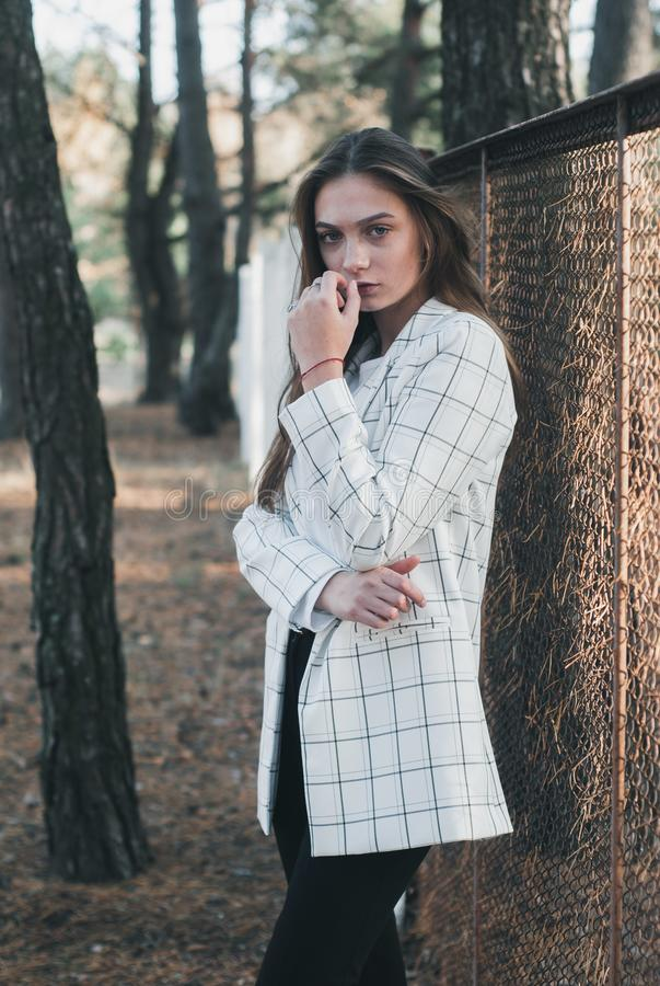 Outdoor Portrait of young beautiful fashionable woman wearing stylish white jacket. Model on the street. Women`s fashion concept stock images