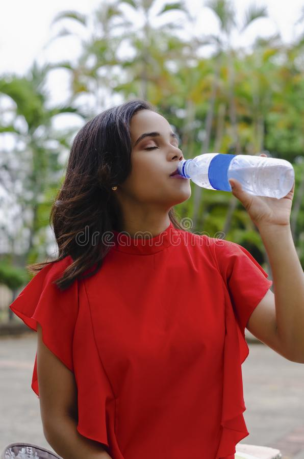 Outdoor portrait of young beautiful girl 19 to 25 years. Brunette. Taken water from a plastic bottle. Wearing red blouse City royalty free stock photography