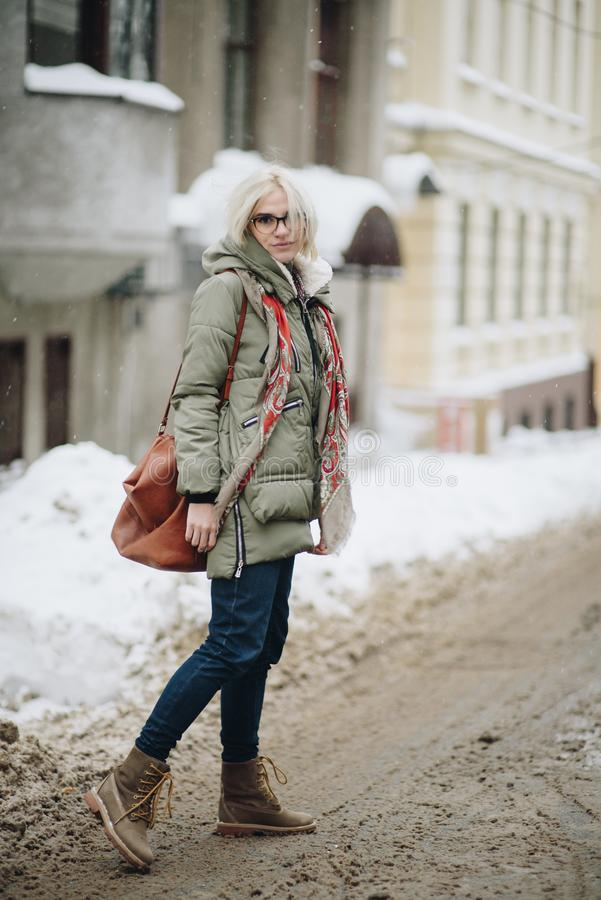 Outdoor portrait of young beautiful happy girl posing on street. Model wearing stylish warm clothes. Magic snowfall. Winter holida royalty free stock photography
