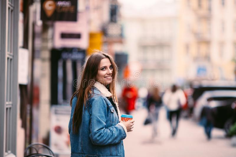 Outdoor portrait of young beautiful happy smiling girl posing on street. Model wearing stylish warm clothes.Keeps coffee. royalty free stock photos