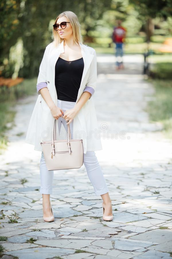 Outdoor portrait of young beautiful happy smiling woman, casual style, walking in city park royalty free stock photo
