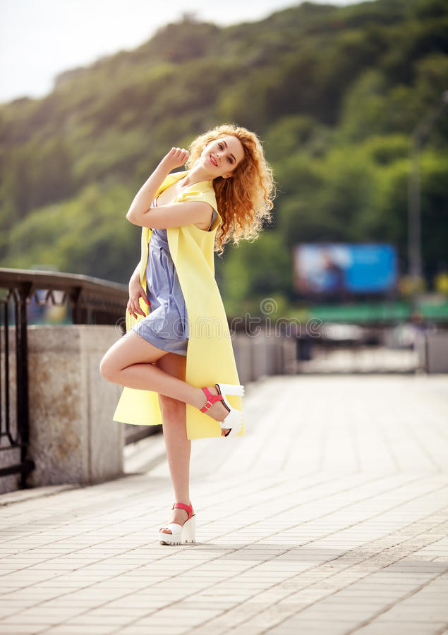 Outdoor portrait of a young beautiful happy smiling woman walking on the street. Model looking at camera. Lady wearing stylish clothes. Sunny day. City royalty free stock image