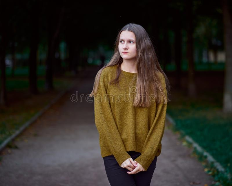 Outdoor portrait of young beautiful stylish woman with long dark hair. Dark art moody fashion portrait of pensive or thoughtful royalty free stock photography