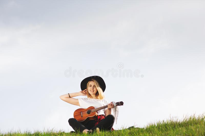 Outdoor portrait of a young beautiful woman in black hat, playing guitar. Space for text royalty free stock images