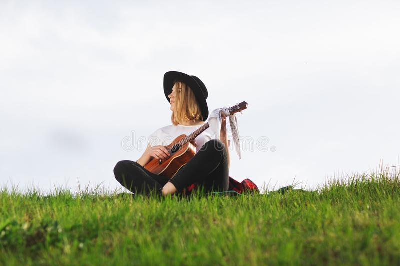 Outdoor portrait of a young beautiful woman in black hat, playing guitar. Space for text stock images