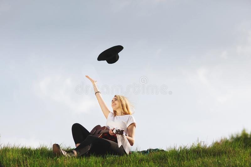 Outdoor portrait of a young beautiful woman in black hat, playing guitar. Space for text stock photos