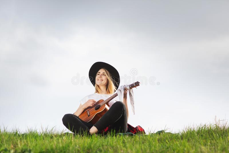Outdoor portrait of a young beautiful woman in black hat, playing guitar. Space for text royalty free stock photography