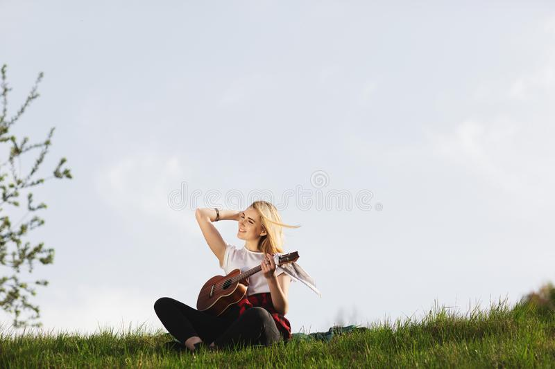 Outdoor portrait of a young beautiful woman in black hat, playing guitar. Space for text stock photography