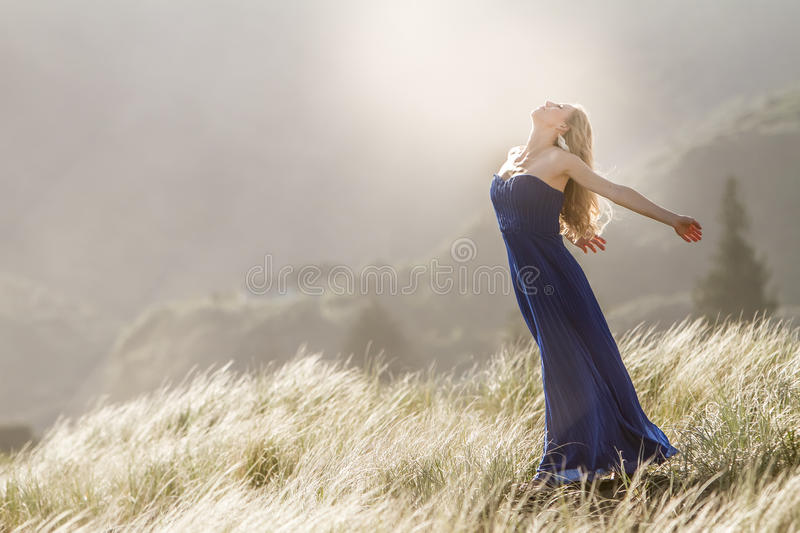 Outdoor portrait of young beautiful woman in blue gown posing on. Outdoor portrait of young beautiful blonde woman in blue gown posing on natural background royalty free stock photo