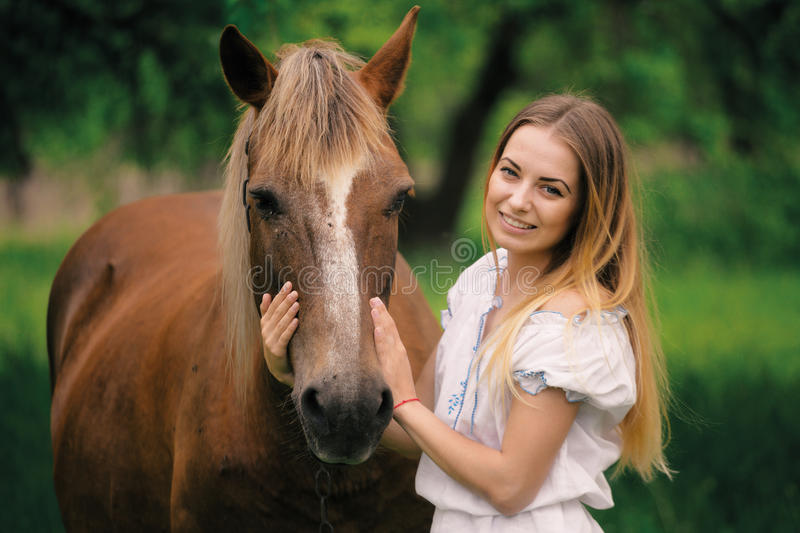 Outdoor portrait of young beautiful woman with horse.  stock photo