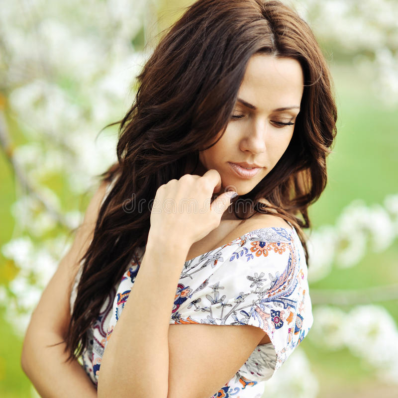 Outdoor portrait of young beautiful woman looking down stock photo