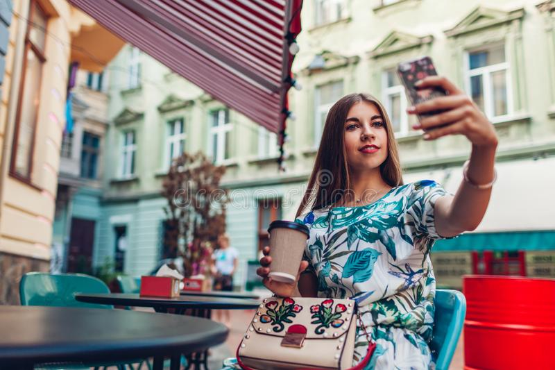 Outdoor portrait young beautiful woman taking selfie using phone. Girl drinking coffee in Lviv cafe. royalty free stock image