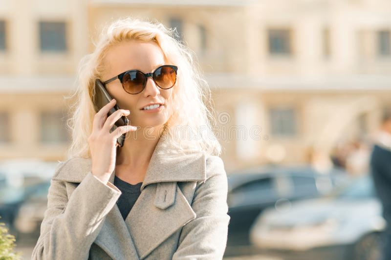Outdoor portrait of young blonde woman with curly hair smiling and talking on a mobile phone on sunny autumn day in the city.  stock photography