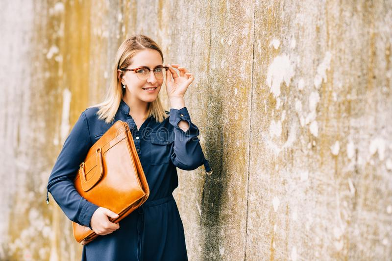Outdoor portrait of young business woman holding brown leather briefcase stock photo